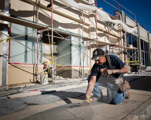 Workers restoring an art deco building/