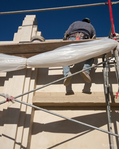 Plasterer sits atop a scaffolding.